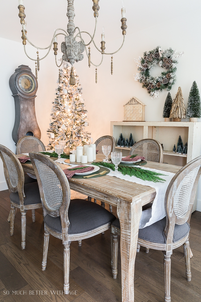 French chandelier and cane backed chairs in dining room decorated for Christmas.