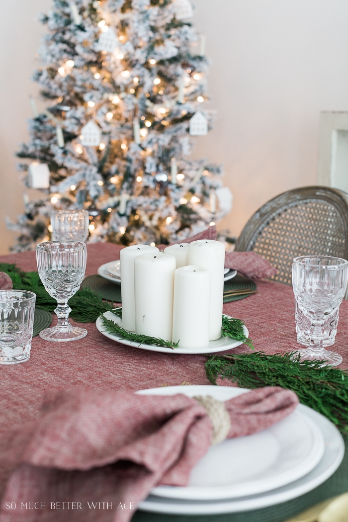 Candles on plate in centre of table with Christmas tree in background.