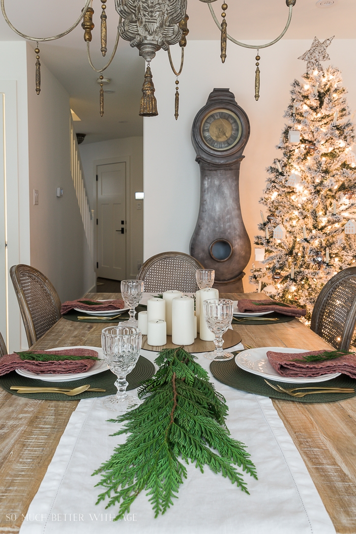 Big clock with greenery on table and Christmas tree in corner.