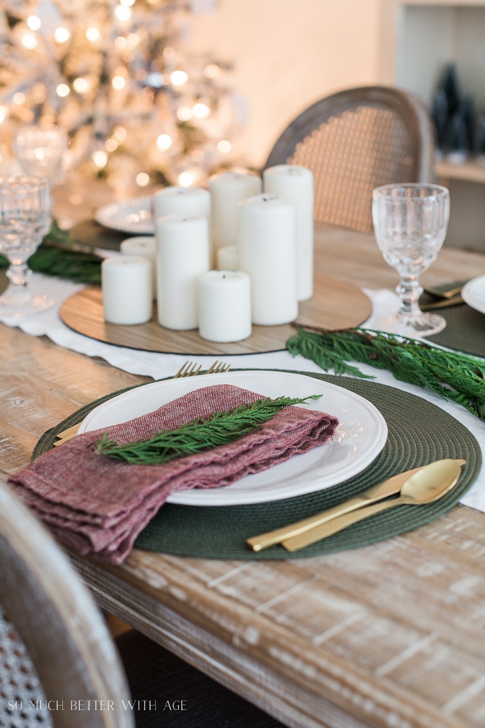 Place setting on table with Christmas tree in background.