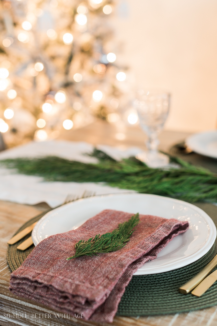 Cedar clipping on red napkin on plate with lights in background.