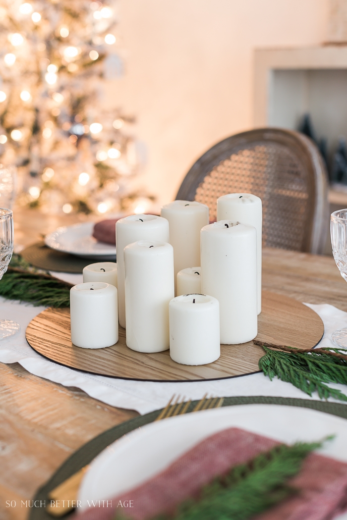 Candles in middle of table with Christmas tree in background.