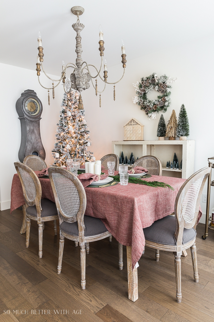 Red tablecloth on table with French chairs, big chandelier and big clock with Christmas tree.