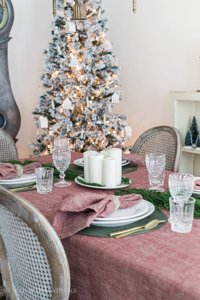 Christmas table with red tablecloth and greenery.
