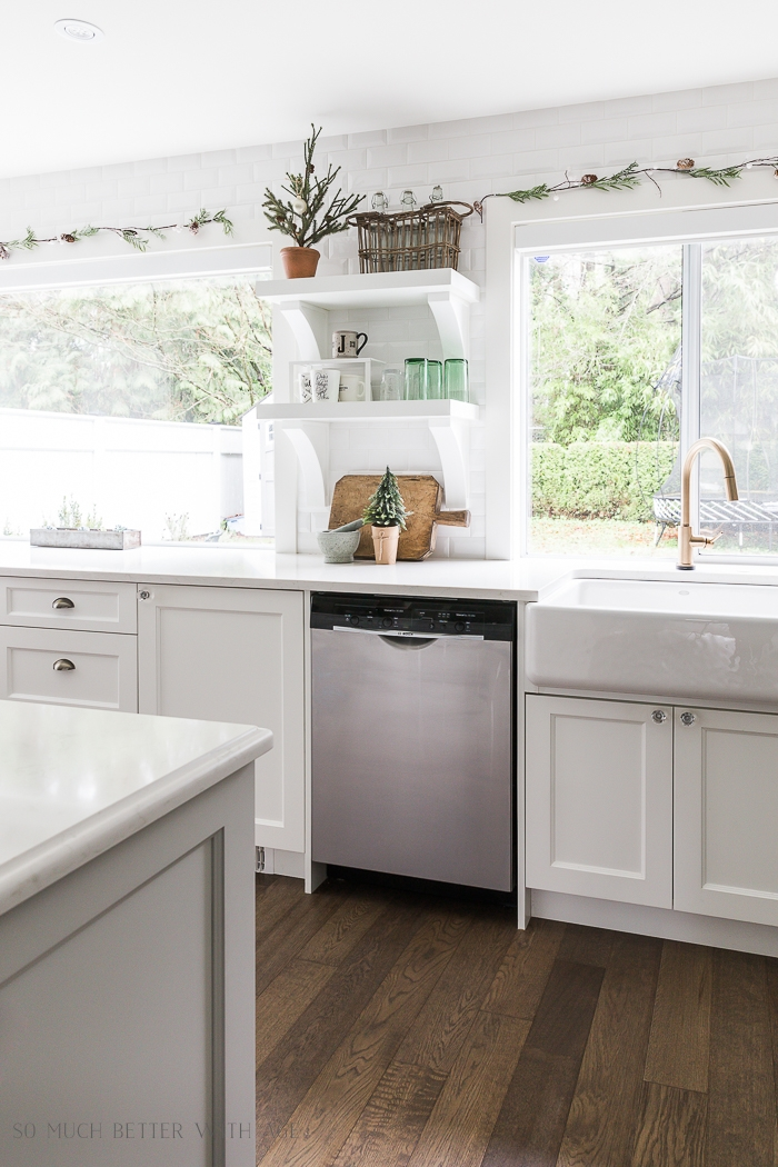 White kitchen with garland above windows.