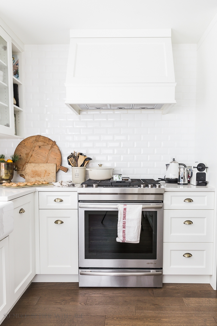 White kitchen, stove, bread boards on counter.