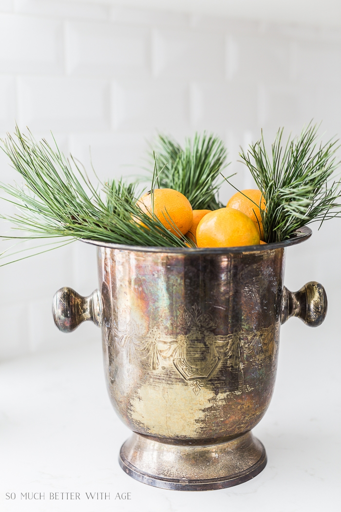 Champagne bucket with oranges and pine clippings.