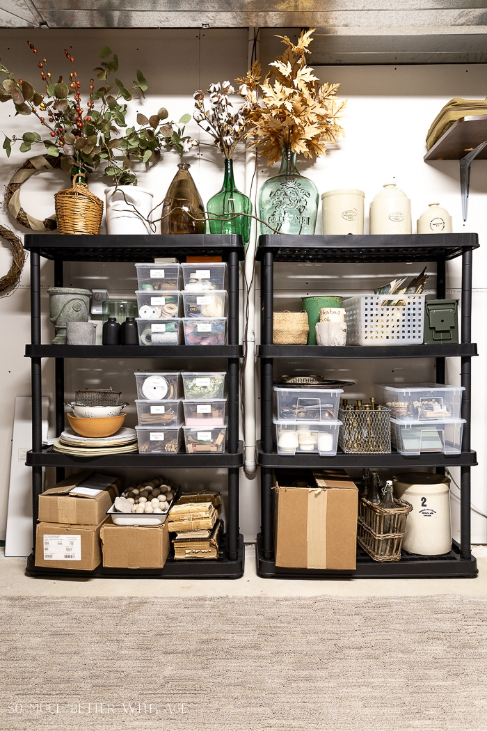 Vases and bins on black shelving units.