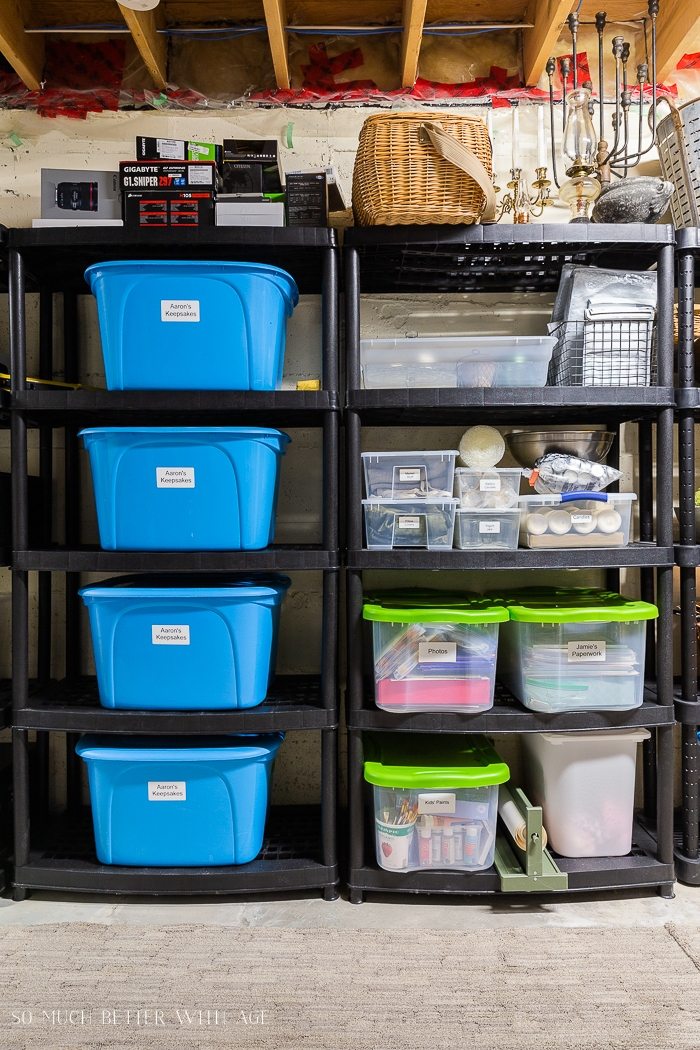 Organized basement with storage bins on black shelving units.