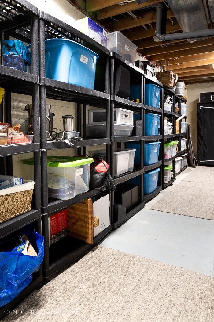 Neat row of shelves against a wall in basement with storage bins.