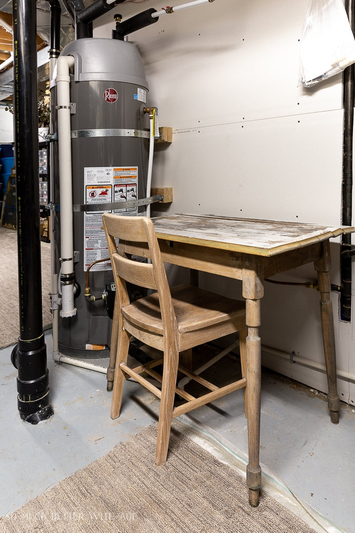 Vintage desk and chair near hot water tank in basement.