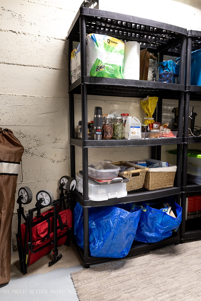 Paper towel and stuff on shelving unit in basement.