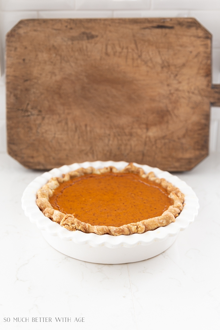Pumpkin pie with bread board leaning on wall in background.