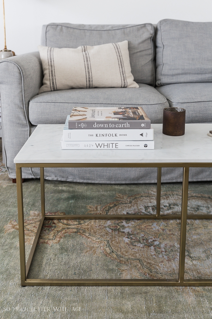 Grey couch and marble and gold coffee with books in front.