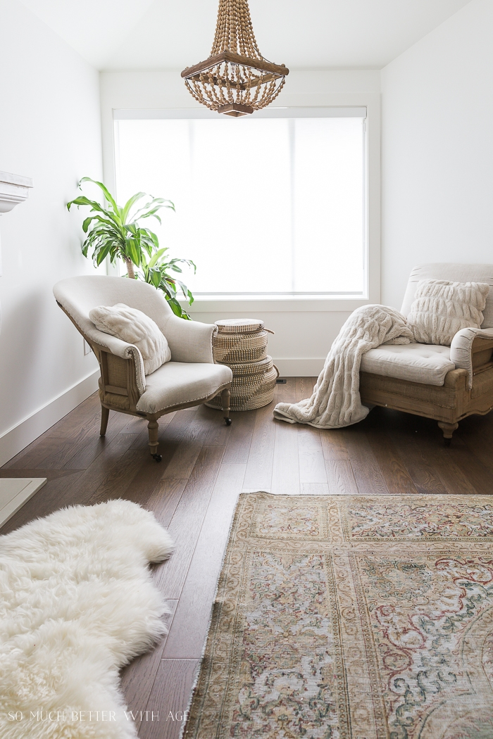 Two armchairs in front of large window in living room.