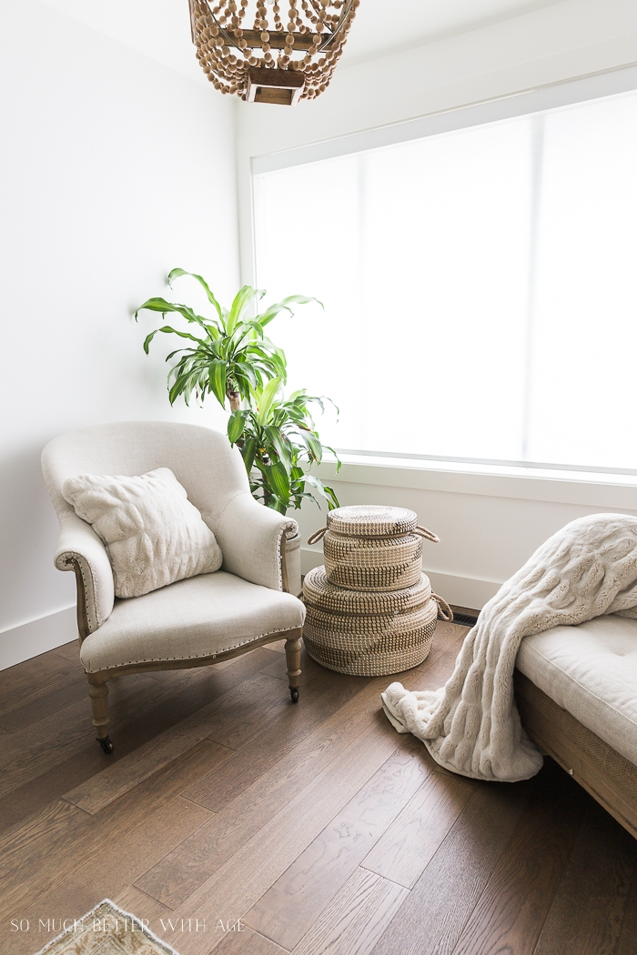Linen covered chairs with fluffy throw blanket and pillow with green plant in corner.