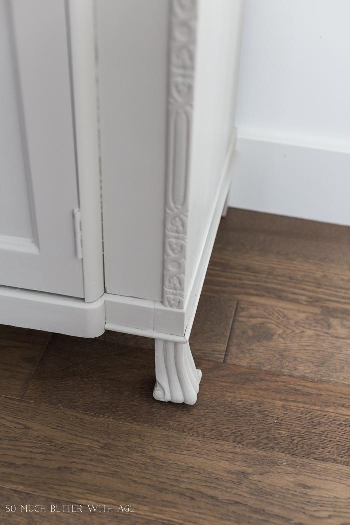 Decorative feet on cabinet.