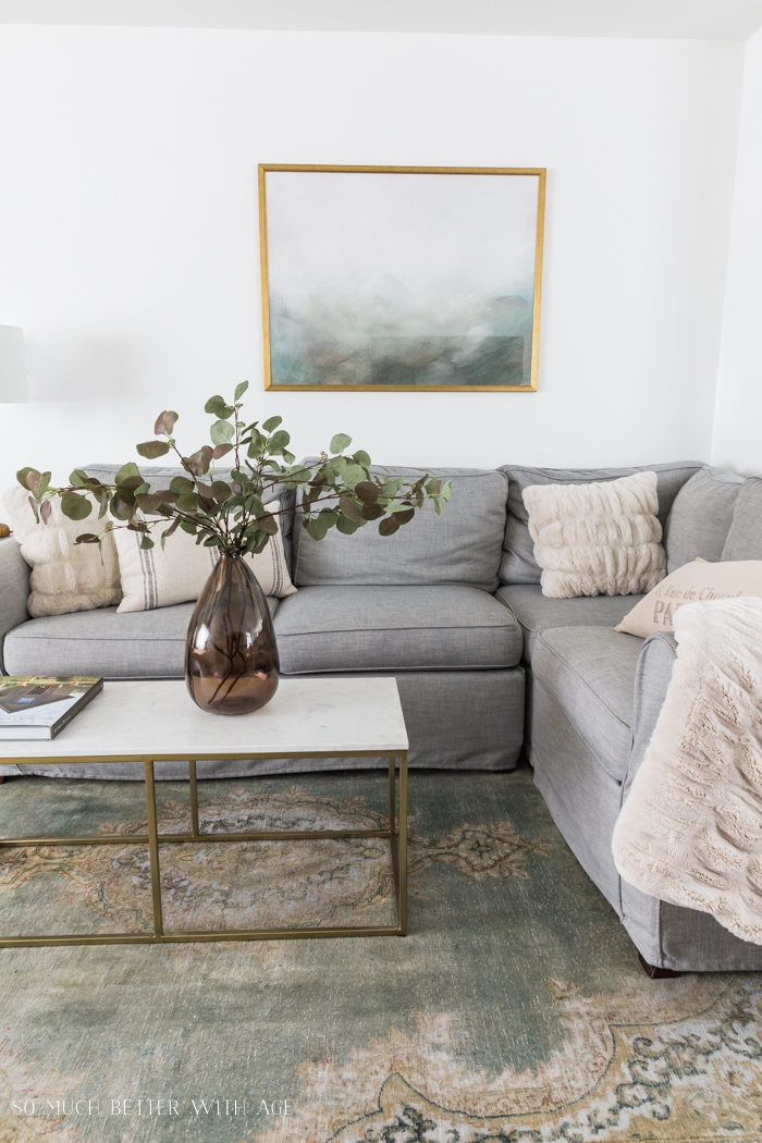 Grey couch, green rug, green and gold artwork and brown vase with greenery on marble and gold coffee table.