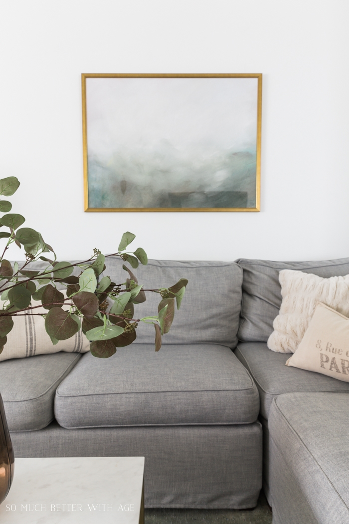 Greenery in vase with gold framed art on wall, grey couch.