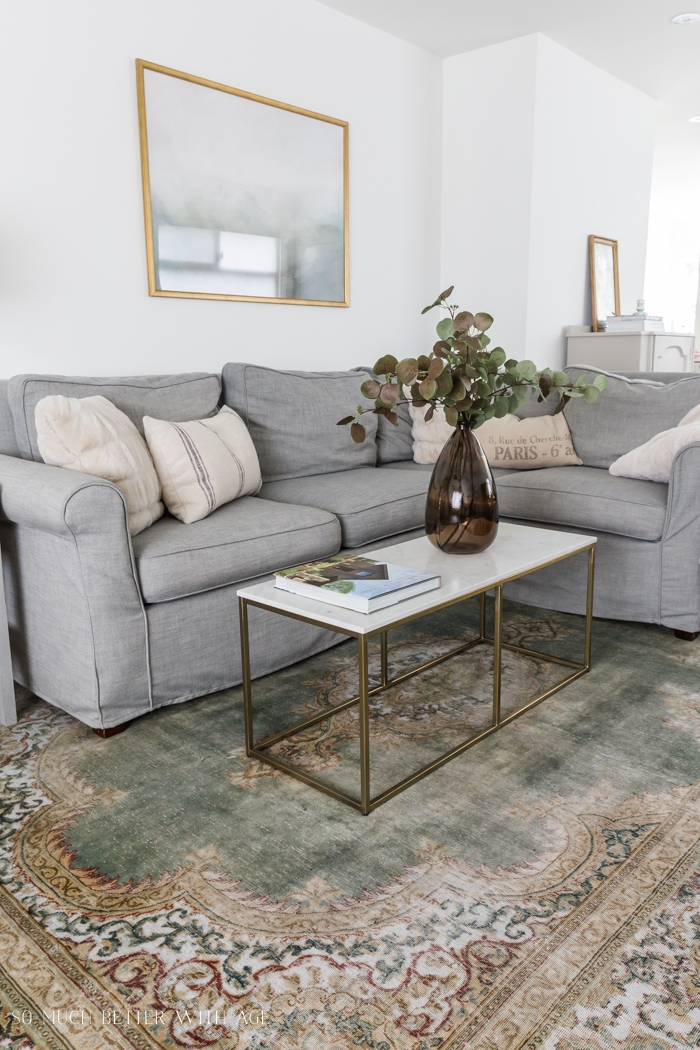 Sectional couch grey with marble coffee table and large brown vase with eucalyptus.