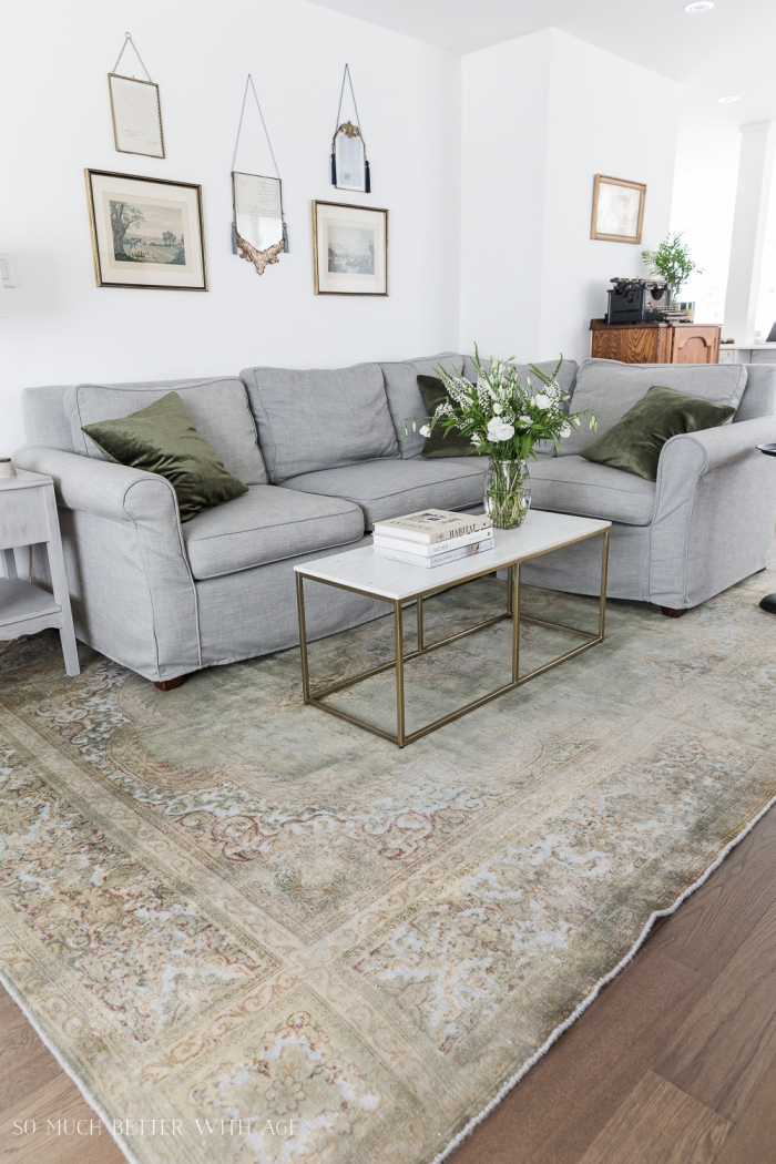 Green vintage rug in living room with grey couch.