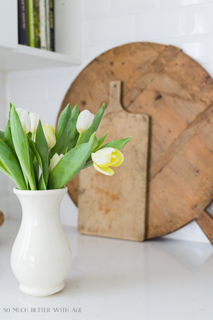 Tulips in cream vase on kitchen counter with wooden boards in background.