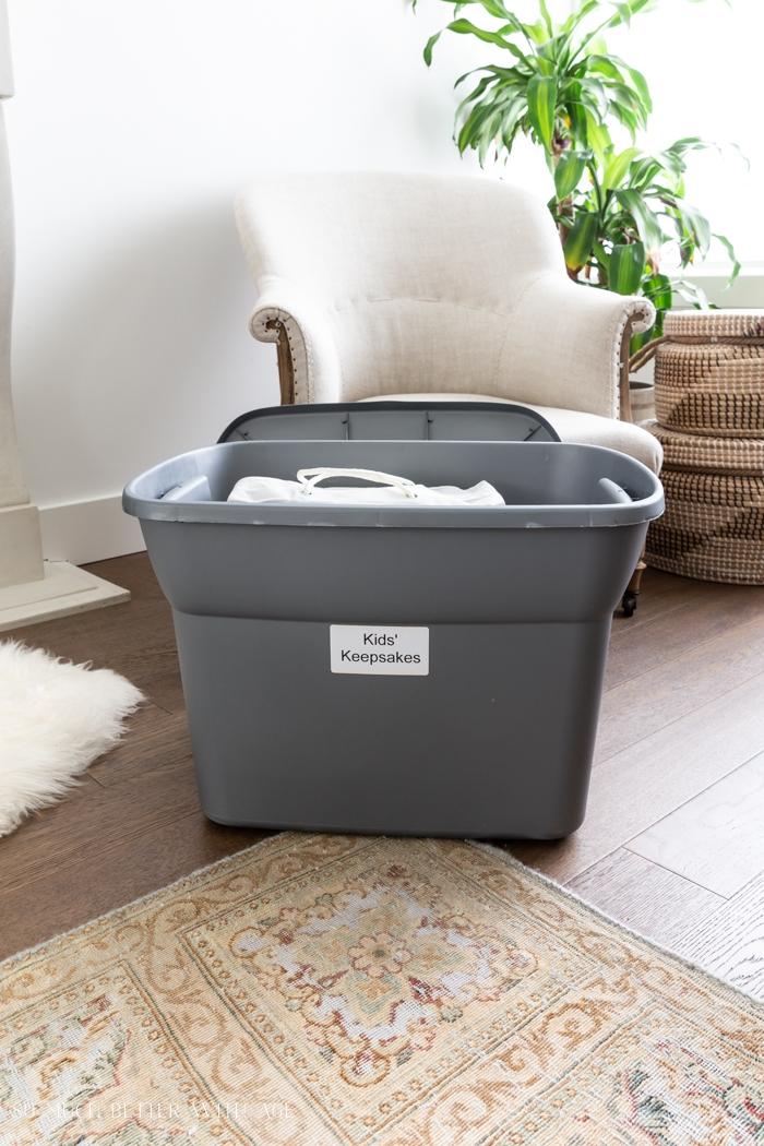 Storage bin with kids' keepsakes label on it.