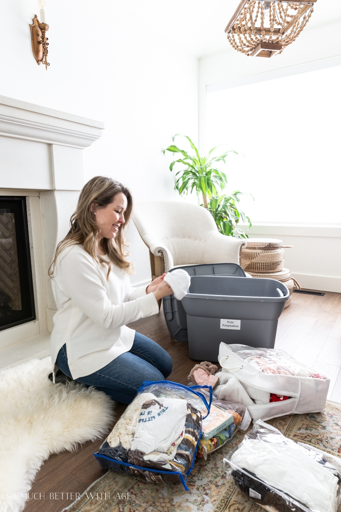 Woman looking at baby clothes in living room.