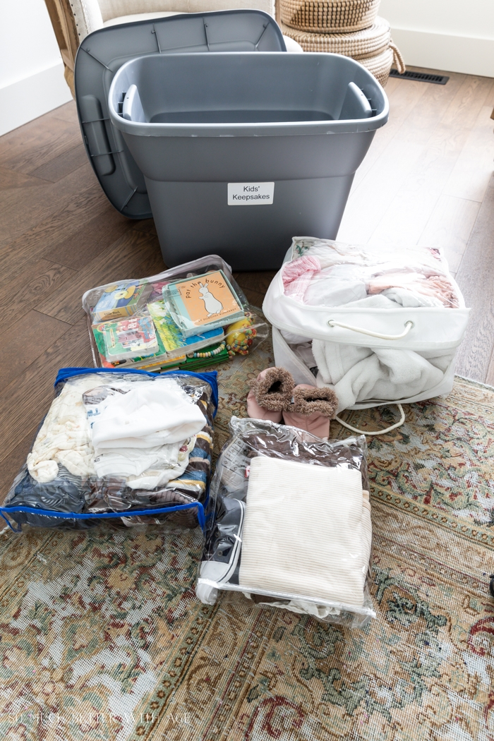 Baby clothes on floor ready to go in storage bin.