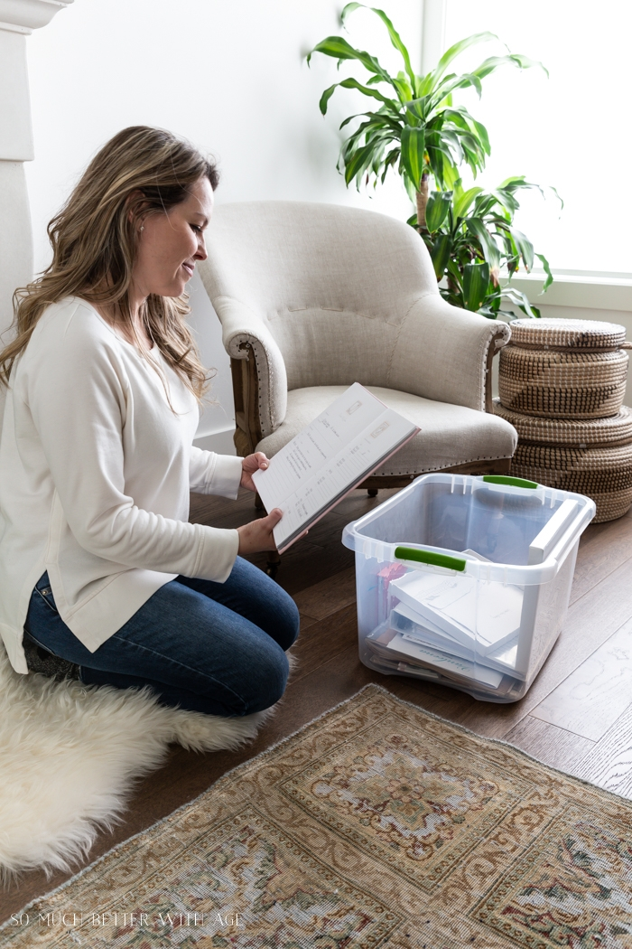 Woman looking at baby book sitting on floor.