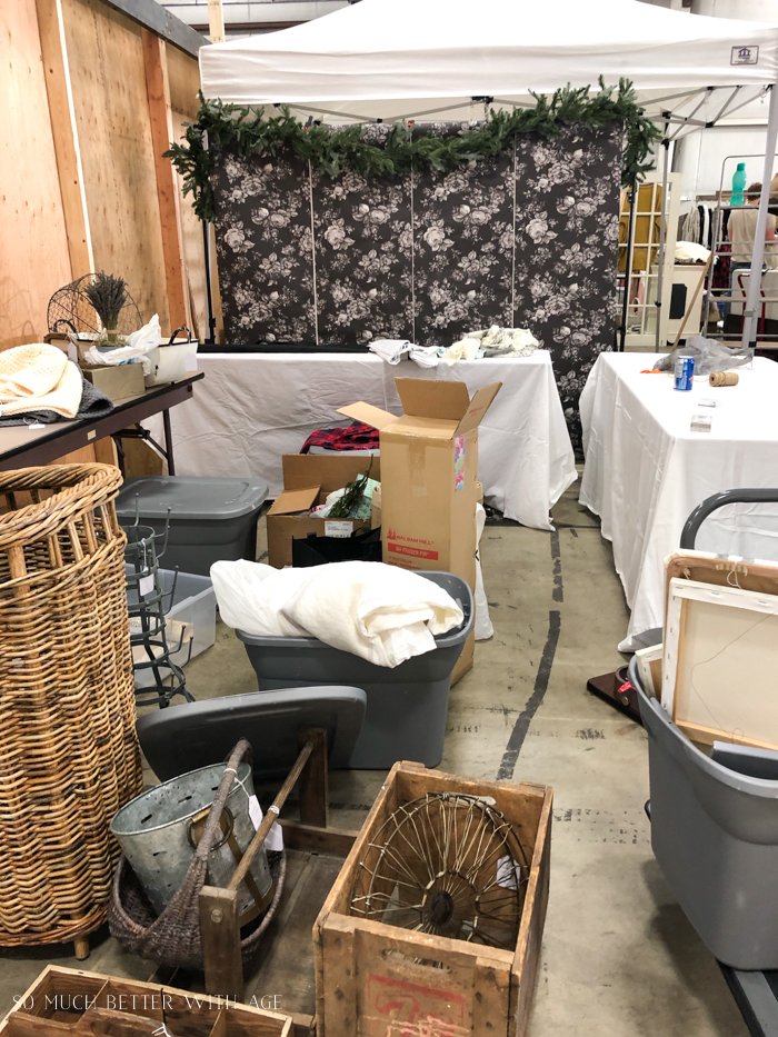 Setting up a booth at a market with lots of vintage stuff around.