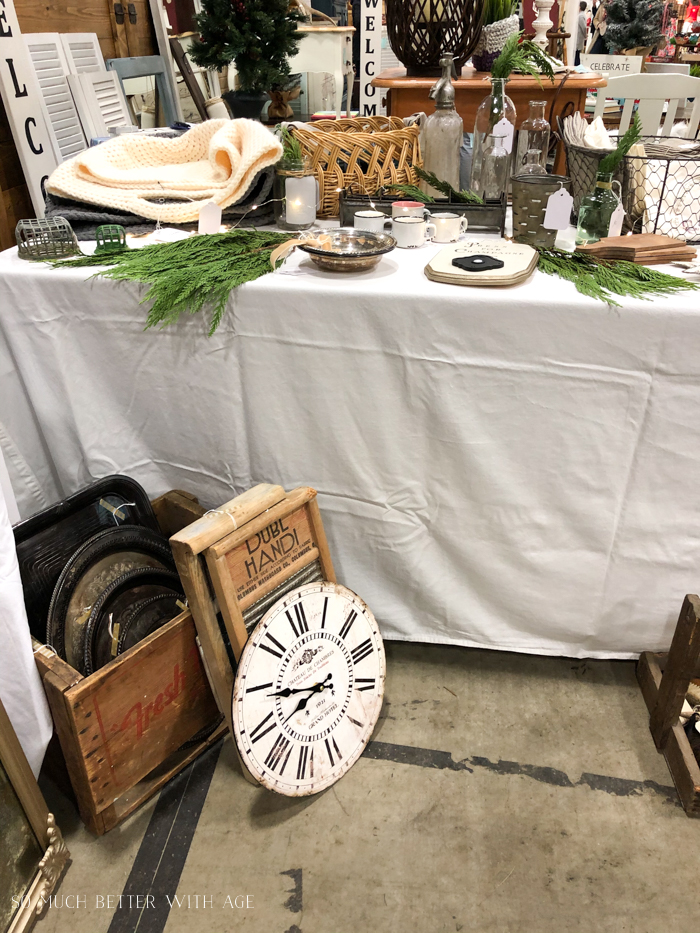 Selling vintage items at a market on tables with white tablecloths.