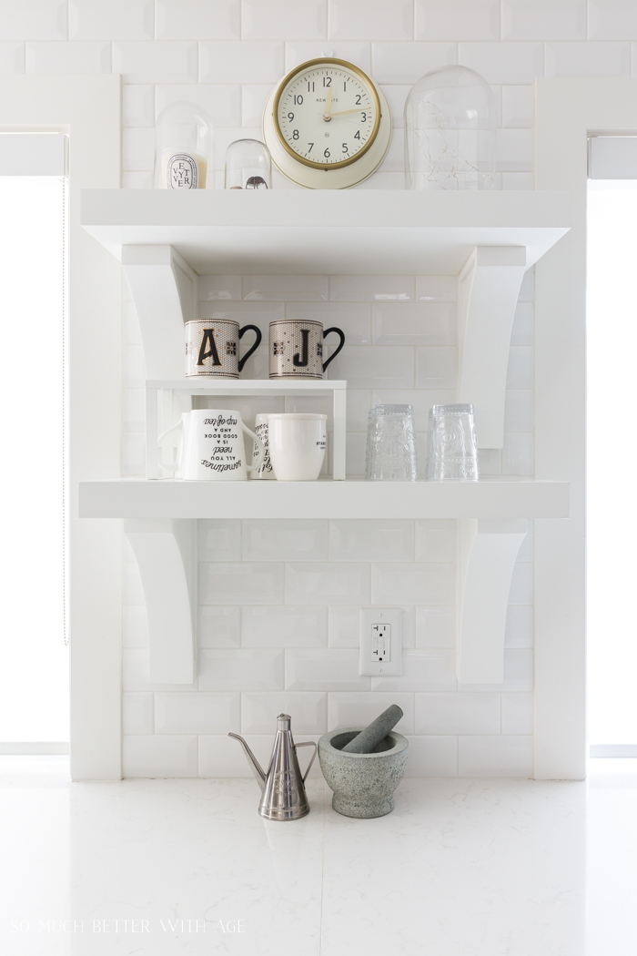 White subway tile, white open shelving in kitchen.