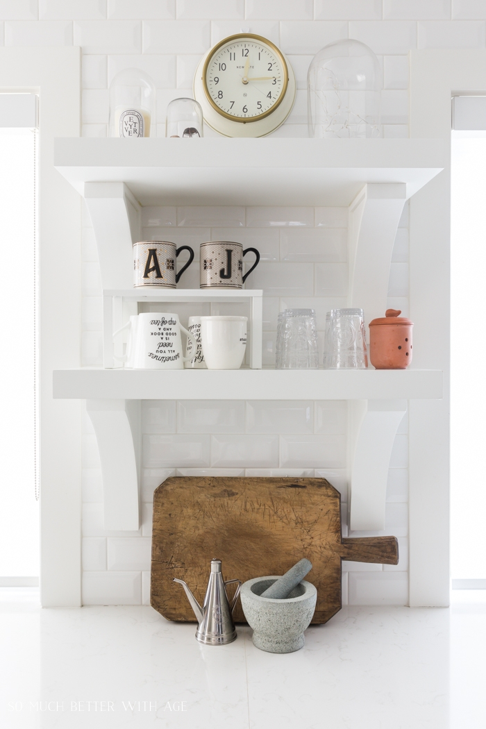 White open shelving with wood cutting board.