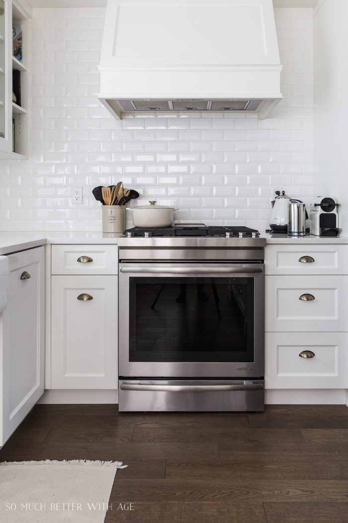 Stove in kitchen with white backsplash in subway tile.