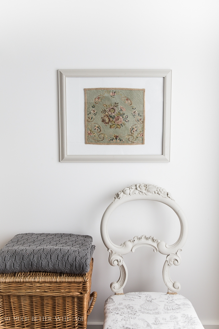 Needlepoint framed on wall with antique chair.