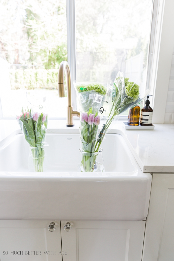 Flowers in plastic wrap sinking in a white sink.