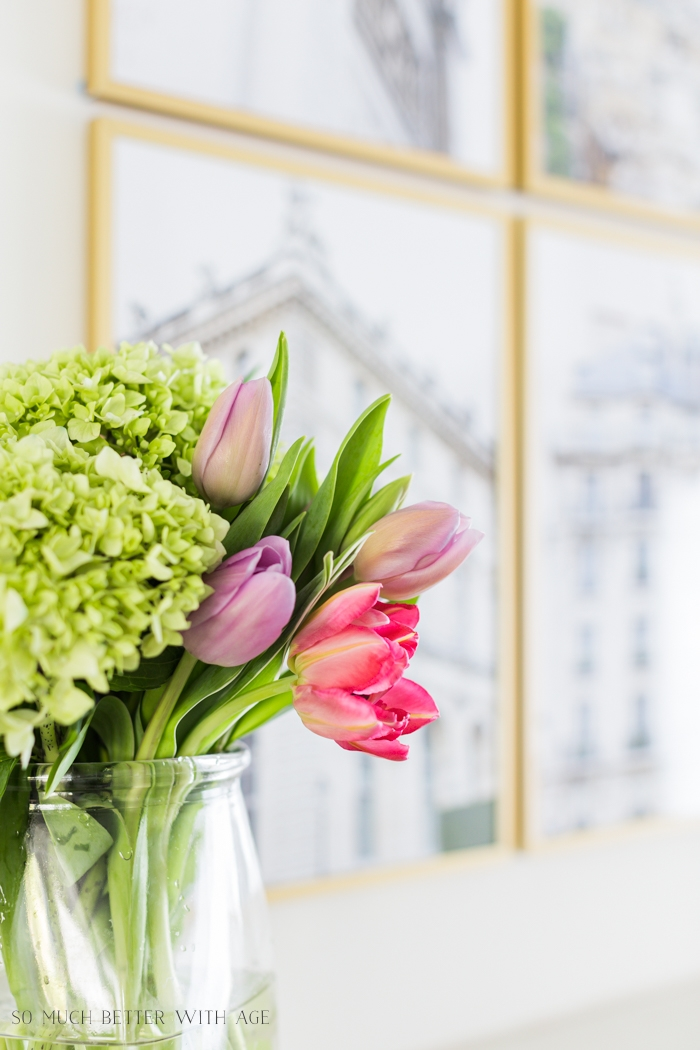 Tulips with framed art behind on wall.