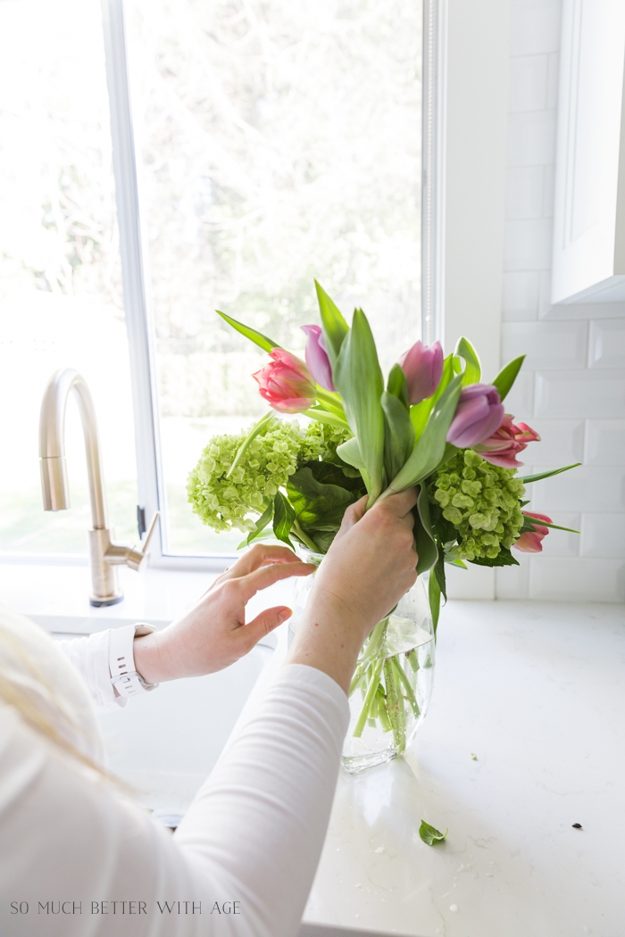 Someone putting tulips in a vase for flower arranging.
