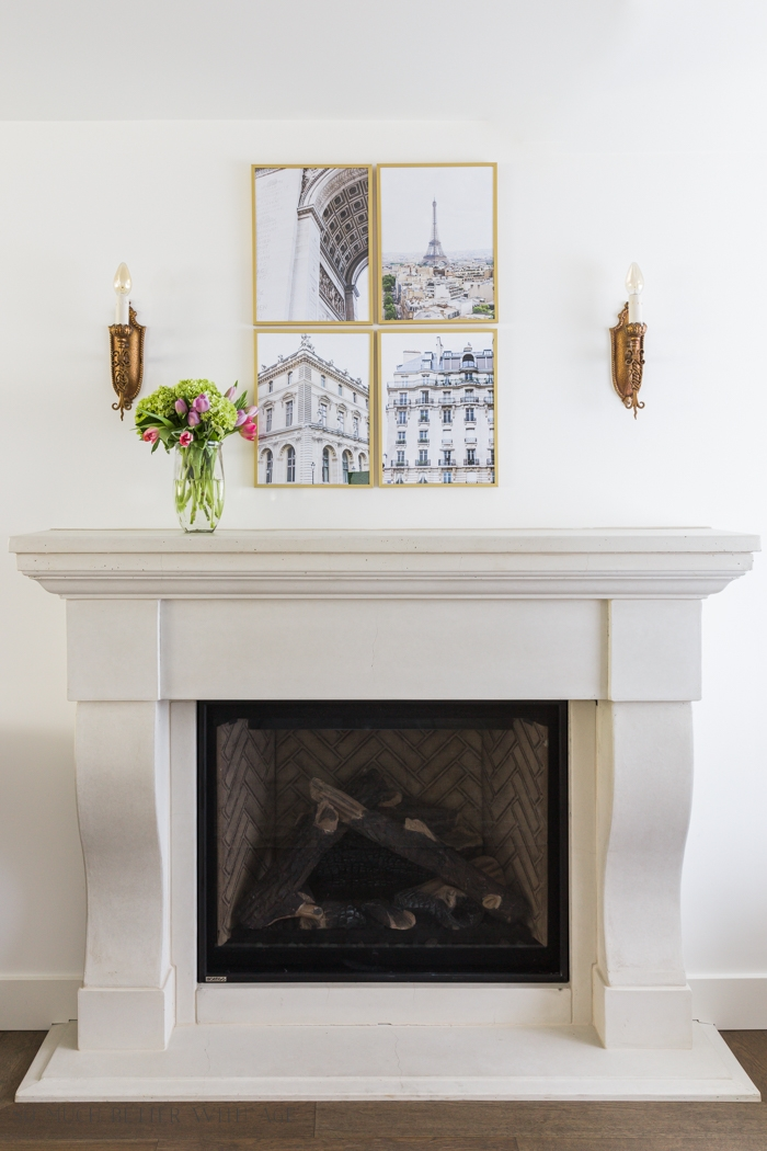 Four pieces of art on wall above fireplace mantel.