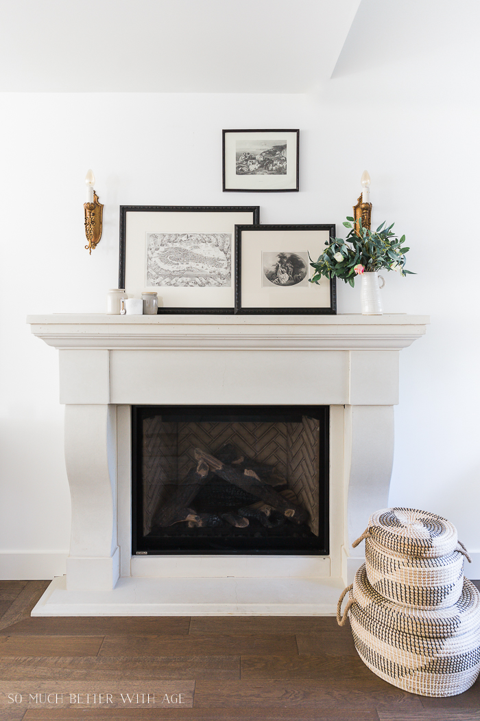 A fireplace mantel with black and white photos on it.