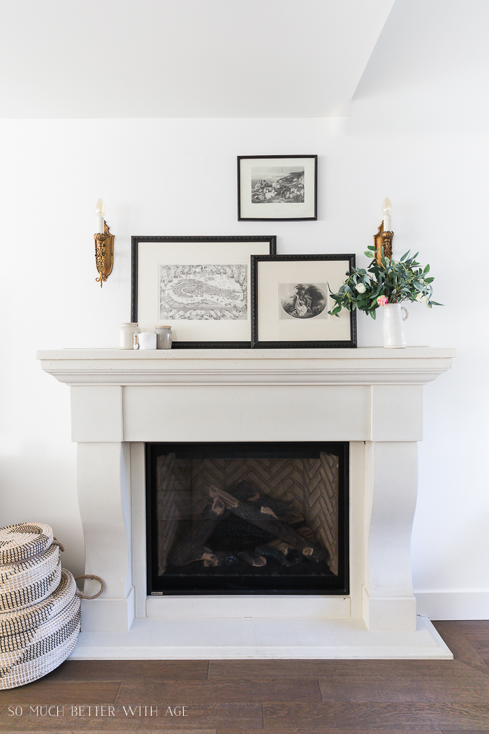 Fireplace mantel with black and white engravings on wall.