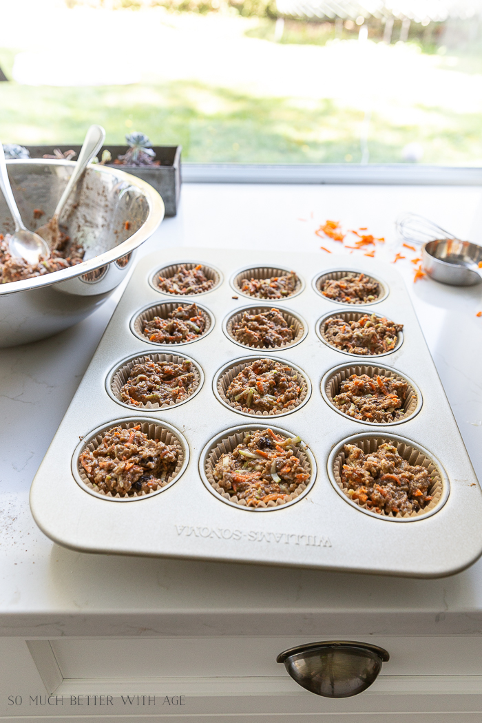 Spooning muffins into cupcake liners.