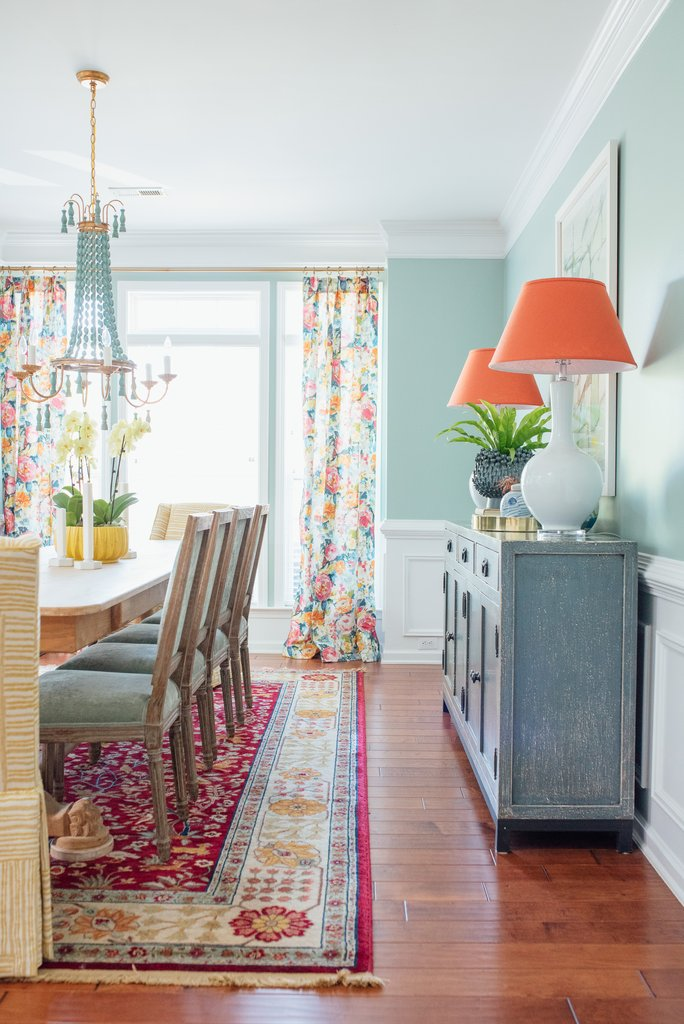 Turquoise walls, coral lamps and rug in dining room from Amanada Louise Interiors.
