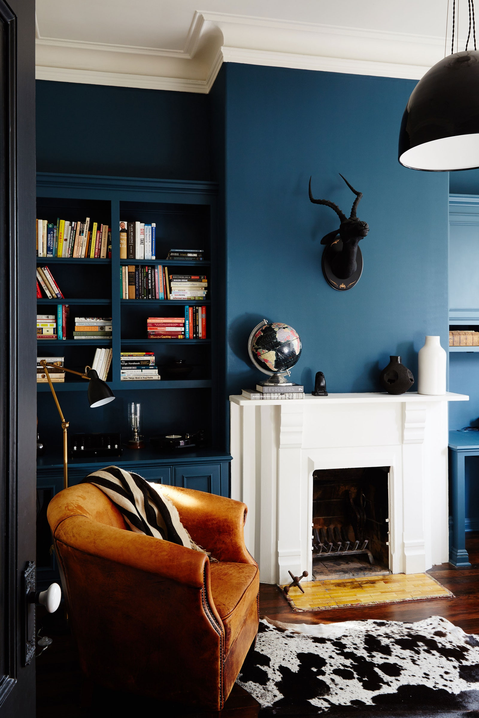 Dark blue walls with fireplace and leather armchair.