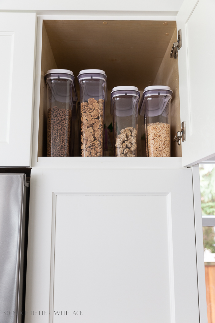 Cereal containers filled with cereal in pantry.