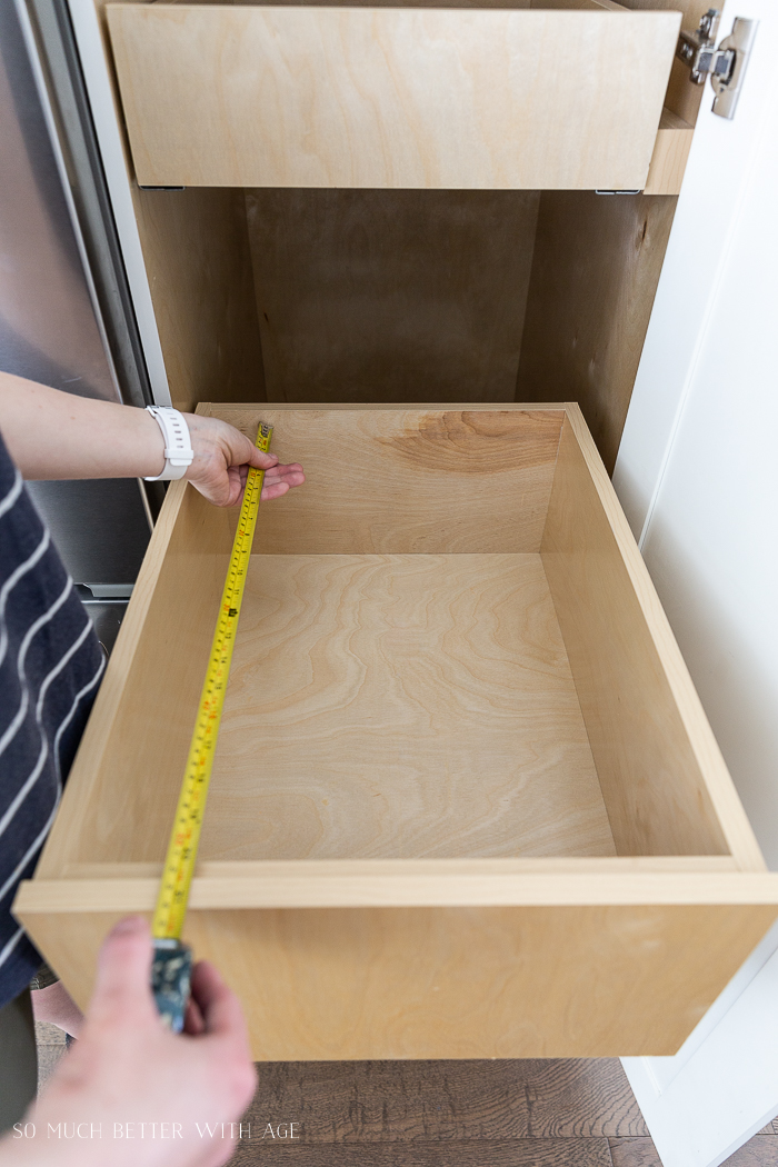 Measuring empty drawer in kitchen with measuring tape.