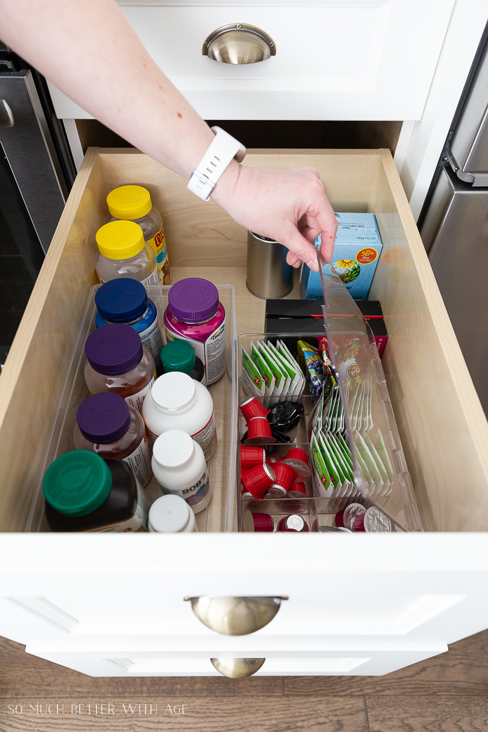Someone holding open a clear bin with coffee pods and tea bags. Vitamin bottles in drawer too.