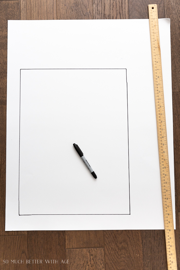 Large white paper with yard stick and sharpie pen and rectangle drawn on.
