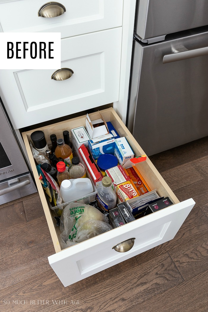 Drawer pulled open in kitchen full with food products.